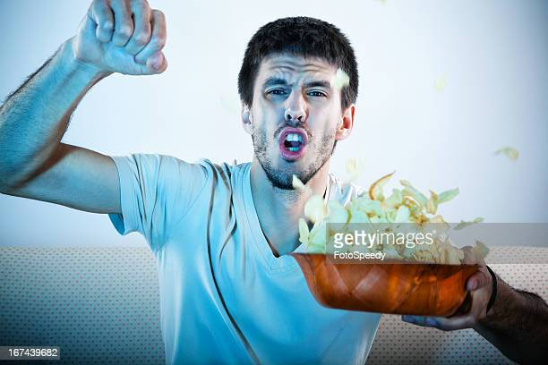 Man watching television with a bowl of chips