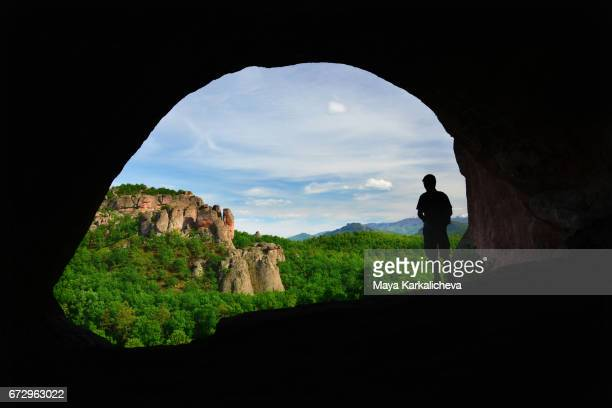 Man watching the landscape from the inside of a cave