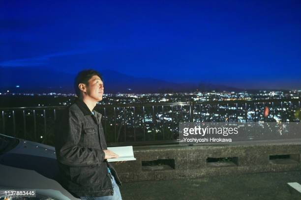 man watching the night view of the city from high ground - 平塚市 ストックフォトと画像