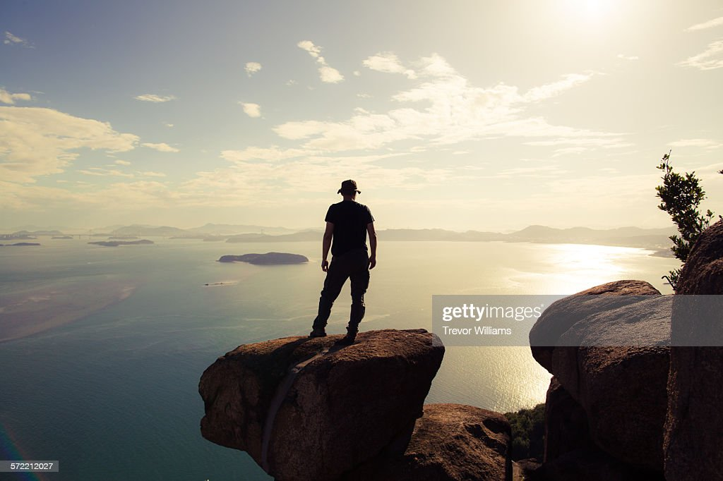 A man watching the sun set from a mountain top : Stock Photo