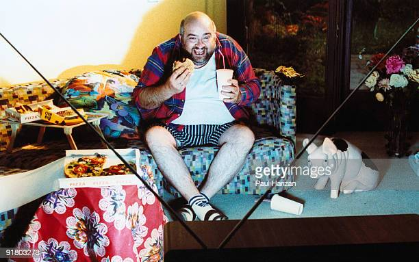 man watching tv and eating junk food - couch potato stock pictures, royalty-free photos & images