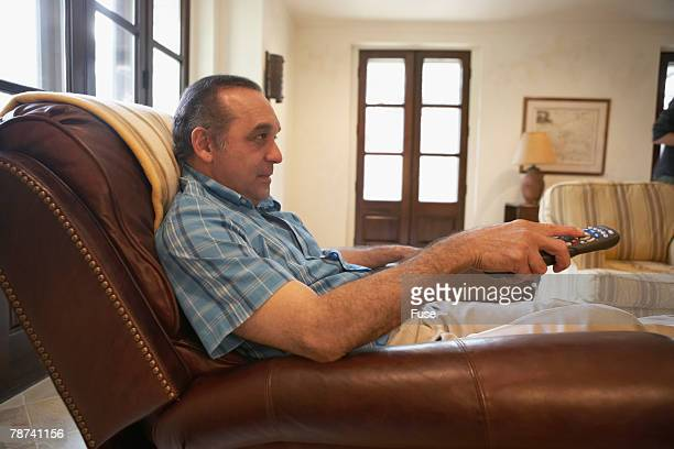man watching tv from recliner - reclining chair stock photos and pictures