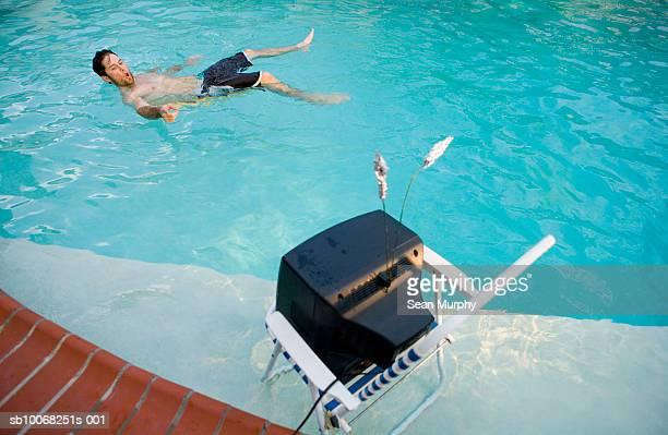 Mann vor dem Fernseher im Swimmingpool
