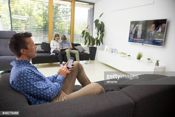 man watching tv - family watching tv stock pictures, royalty-free photos & images