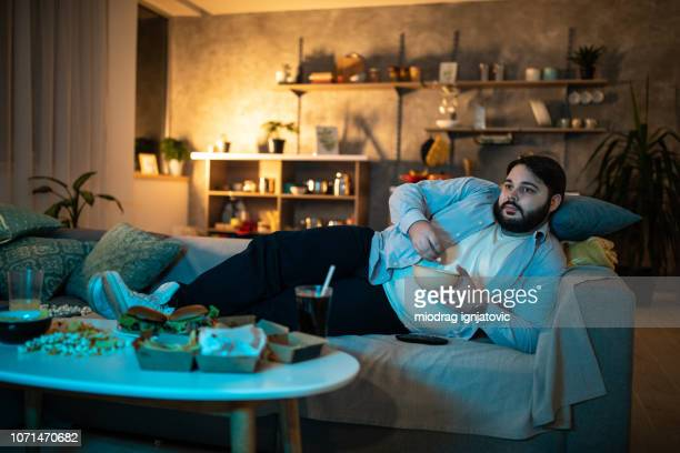 man watching tv show - sofa stock pictures, royalty-free photos & images