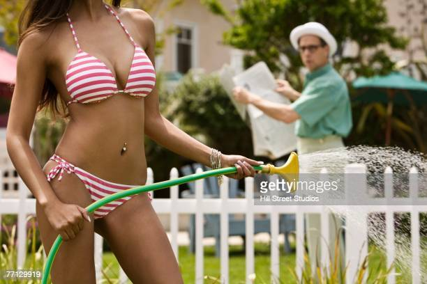 Man watching woman in bikini water plants