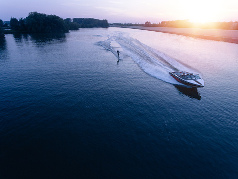 Man water skiiing on lake behind a boat 637069654