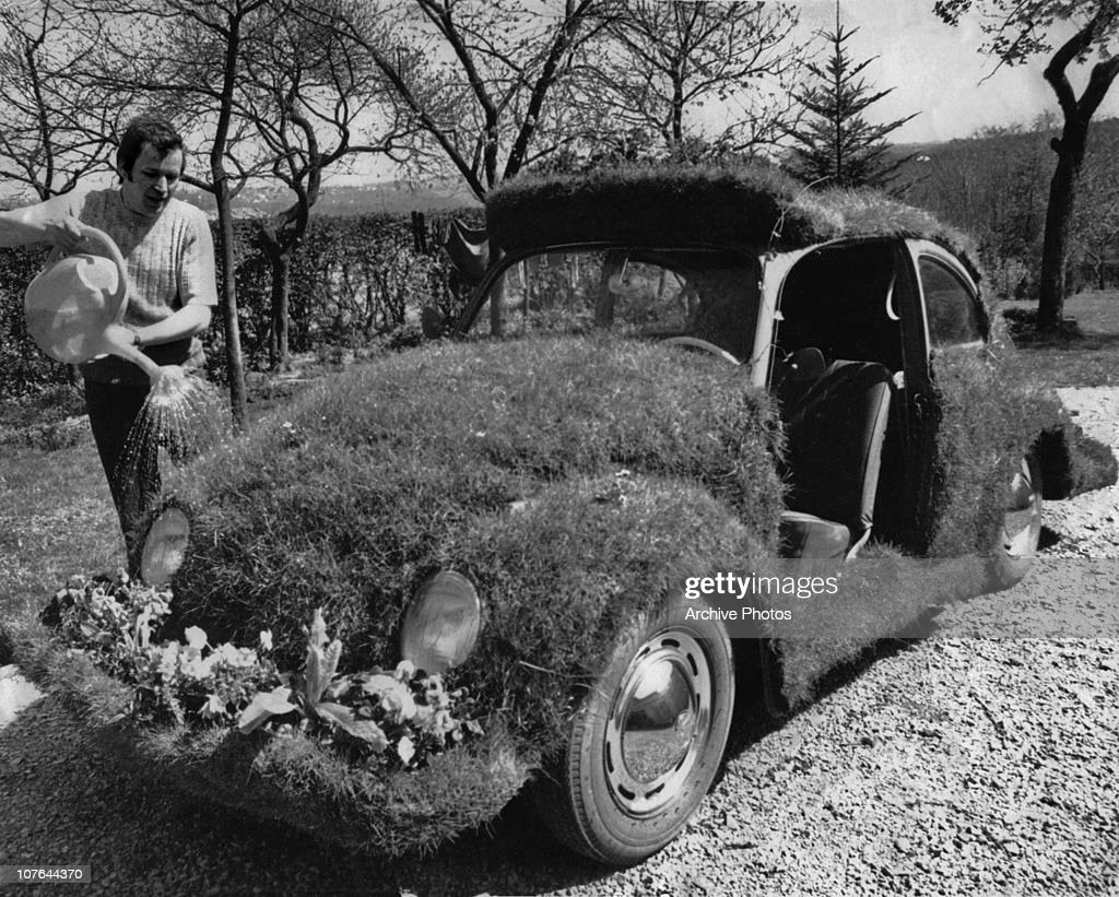 A man watering grass growing on a turfed-over Volkswagen Beetle car, circa 1970. Spring flowers have been planted on the front bumper area.
