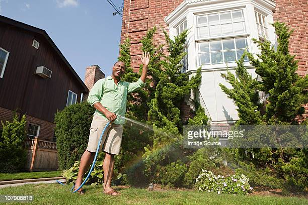 man watering grass with hosepipe - watering stock pictures, royalty-free photos & images