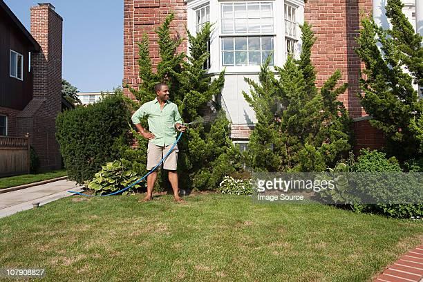 Homme arroser l'herbe avec hosepipe