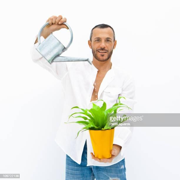 Mann gießen einer Pflanze