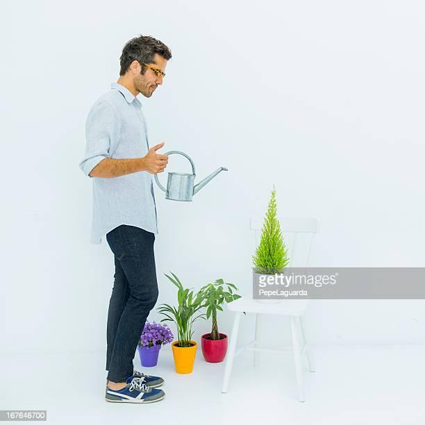 Mann gießen seine Pflanzen in einem weißen Heimtrikot
