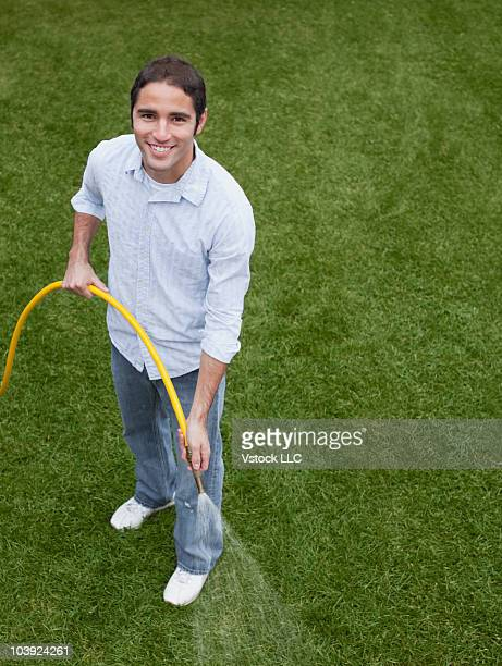 Man watering the lawn with garden hose