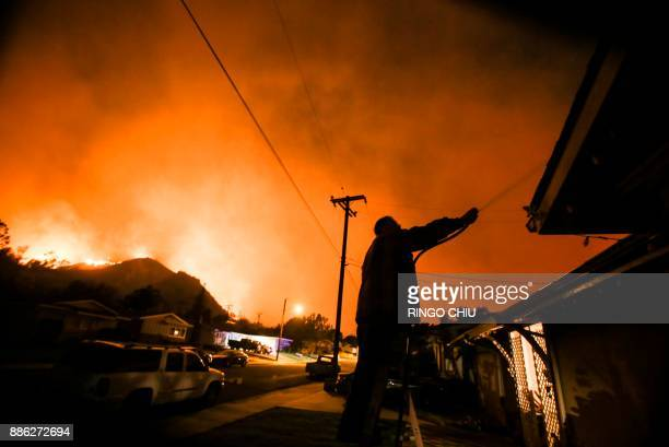 A man waters his home as firefighters battle a wildfire as it burns along a hillside near homes in Santa Paula California on December 5 2017...