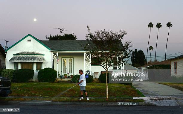 A man waters the lawn and sidewalk in front of his house beneath an almost full moon during the early evening in Monterey Park Los Angeles County on...