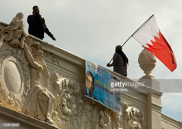 Man waves a Bahraini national flag from the top of the Bahraini Embassy in central London on April 16, 2012 during a protest over the imprisonment of...