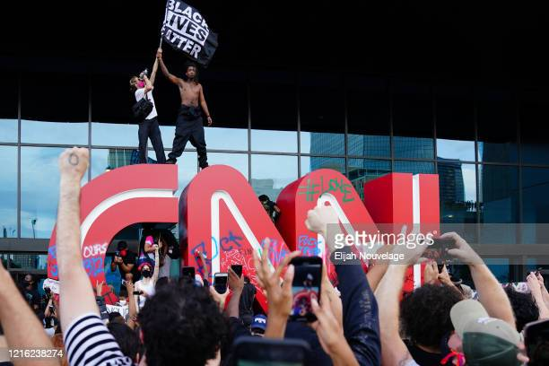 A man waves a Black Lives Matter flag atop the CNN logo during a protest in response to the police killing of George Floyd outside the CNN Center on...