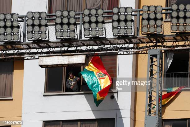 Man waves a Bolivian flag from a building next to Hernando Siles Stadium before a match between Bolivia and Argentina as part of South American...