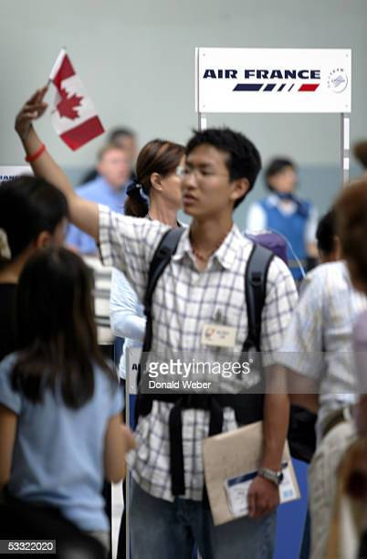 A man waves a Canadian flag while checking in for an Air France flight to Paris at Pearson International Airport August 3 2005 in Toronto Canada Air...