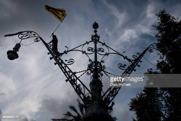 A man waves a Catalan flag after climbing a light post ahead of the speech by Catalan President Carles Puigdemont outside the Parliament of Catalunya...