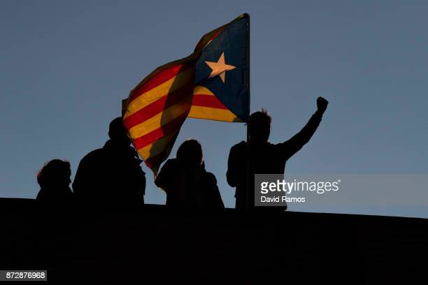 A man waves a Catalan Independence flag know as 'Estelada' on a roof of a building during a demonstration on November 11 2017 in Barcelona Spain...