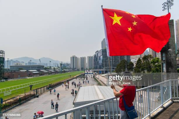 Man waves a China flag at the racecourse during the National Day celebrations to mark the 70th anniversary of communist China's founding on October...