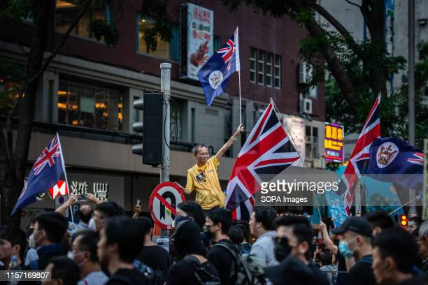 A man waves a colonial flag surrounded by British flags during the demonstration Tens of thousands of protesters took to the street of Hong Kong in...