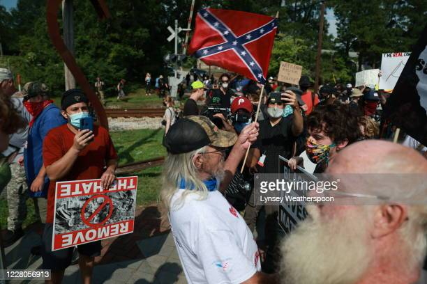 Man waves a confederate flag towards a crowd of anti-racists protestors on August 15, 2020 near the downtown of Stone Mountain, Georgia. Georgia's...
