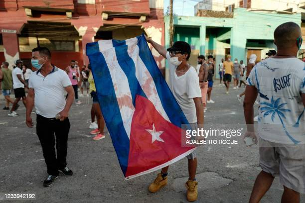 Man waves a Cuban flag during a demonstration against the government of Cuban President Miguel Diaz-Canel in Havana, on July 11, 2021. - Thousands of...
