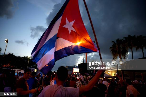 Man waves a Cuban flag in the street near of Versailles, a Cuban restaurant in the Little Havana neighborhood, at a demonstration in support of the...