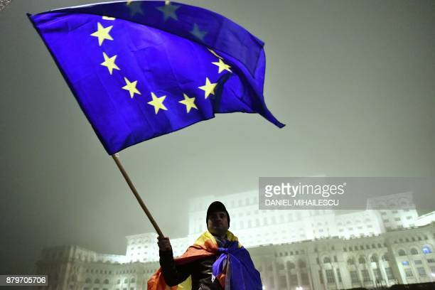 Man waves a European Union flag in front of the Romanian Parliament headquarters during a protest against government and corruption in the front of...