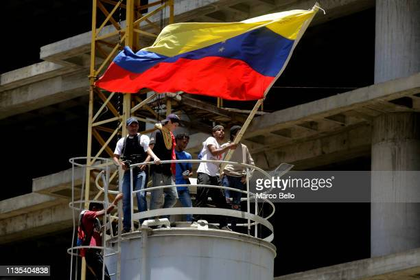Man waves a flag as people attend a rally with Venezuelan opposition leader Juan Guaido on April 6, 2019 in Caracas, Venezuela. Venezuelan opposition...