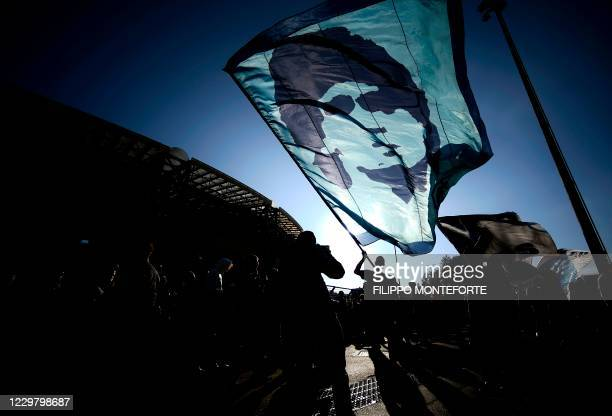 Man waves a flag at the effigy of late Argentinian football legend Diego Maradona, as people gather on November 26, 2020 outside the San Paolo...