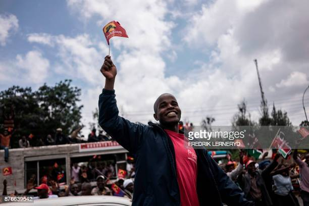 A man waves a flag of President Uhuru Kenyatta's party Jubilee tuko pamoja as he takes part in a demonstration with supporters of Kenyatta to...