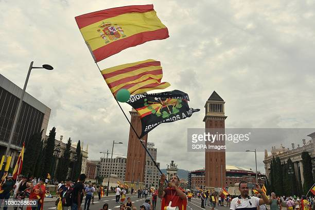A man waves a flag of Spain Catalonia and the Spanish Legion during the demonstration in favor of the unity of Spain Some 2000 people according to...