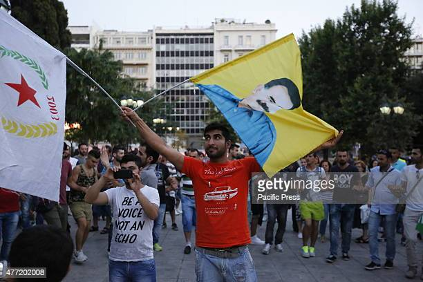 SQUARE ATHENS ATTICA GREECE A man waves a flag with the picture of Abdullah Öcalan on it and a flag of the Democratic Union Party from Syria at the...