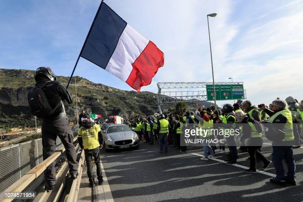 A man waves a French flag as other protestors wearing a yellow vest demonstrate on December 22 in Ventimiglia near the FrenchItalian border as...