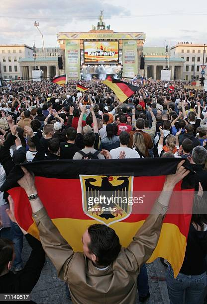 A man waves a German flag among fans gathered for the opening party of the FIFA World Cup 2006 in the Fan Fest in front of the Brandenburg Gate June...
