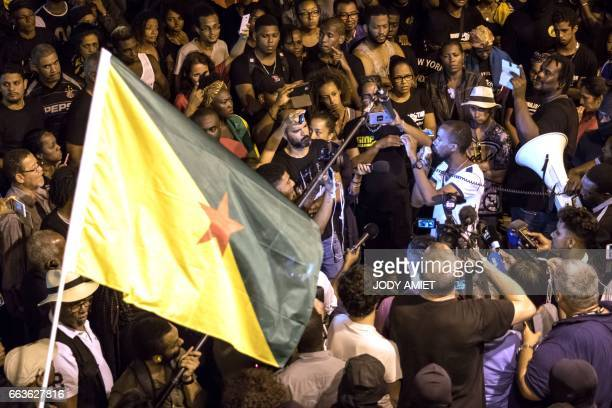 A man waves a Guyanese flag as Guiana workers union secretary general Davy Rimane adresses the protesters after negotations between Guyanese...