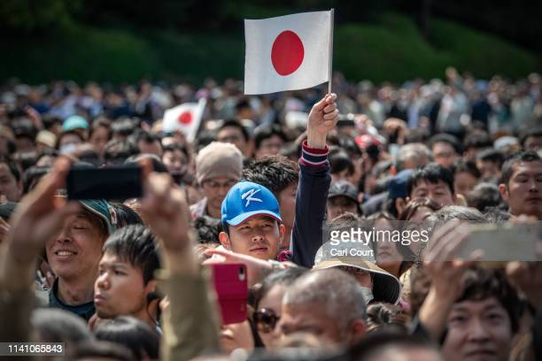 A man waves a Japanese flag as he waits in the grounds of the Imperial Palace ahead of a public address by Emperor Naruhito of Japan on May 4 2019 in...