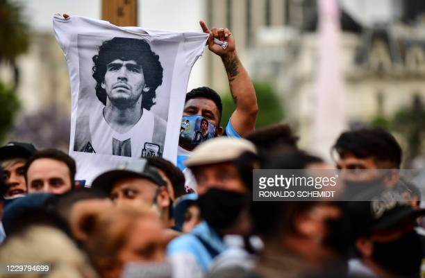 Man waves a jersey with a picture of Diego Maradona as fans wait to enter the Government House to pay tribute to late football legend Diego Armando...