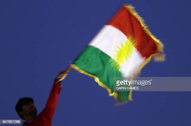 A man waves a Kurdish flag during an event to urge people to vote in the upcoming independence referendum in Arbil the capital of the autonomous...