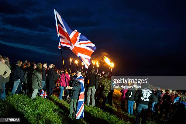 Man waves a large Union Jack flag as The Diamond Jubilee Beacon is lit ontop of Otley Chevin - a high point on the outskirts of Leeds, West...