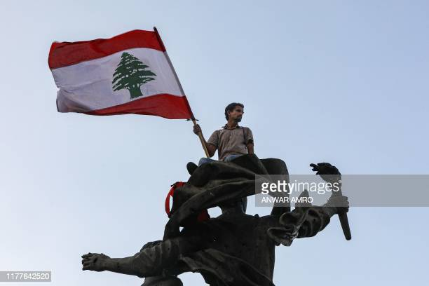 TOPSHOT A man waves a Lebanese national flag as he sits atop the Martyrs' Monument during a demonstration on the sixth day of protest against tax...