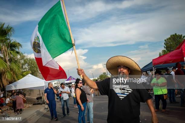Man waves a Mexican flag at a memorial outside Cielo Vista Walmart in El Paso, Texas, U.S., on Wednesday, Aug. 7, 2019. Donald Trump sought to...