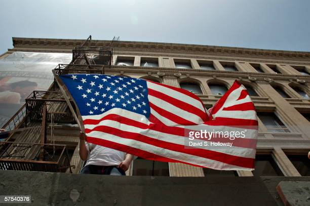 A man waves a mexican flag from a building as hundreds of thousands of immigrants demonstrate on May 1 2006 in downtown Los Angeles California The...