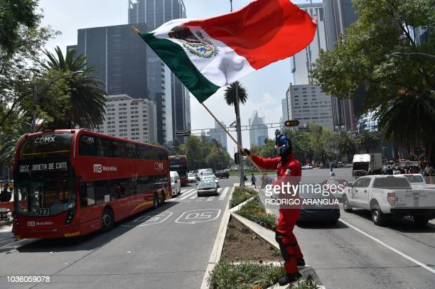 TOPSHOT A man waves a Mexican flag in Mexico City on September 19 2018 as Mexico marks the anniversaries of two deadly earthquakes that hit the...