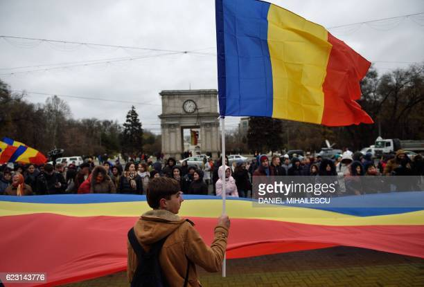 A man waves a Moldovan flag next to others holding a giant Moldovan flag during a protest in downtown Chisinau against what they consider to be a...