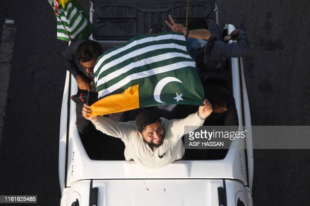 A man waves a Pakistanadministered Kashmir flag as he takes part in Independence Day celebrations in Karachi on August 14 as the nation marks the...