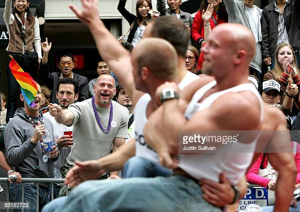 Man waves a pride flag as men pass by on a float during the 2005 San Francisco Pride Parade June 26, 2005 in San Francisco, California. Tens of...